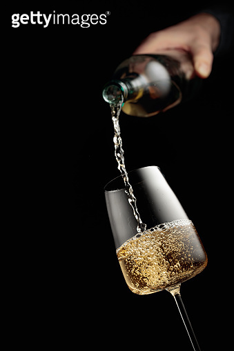 Pouring white wine in a glass goblet.
