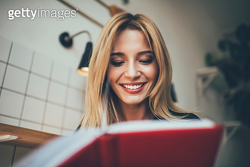 Happy Caucasian female student enjoying leisure time for reading literature book with positive plot, cheerful hipster girl holding education textbook and smiling while checking noted information
