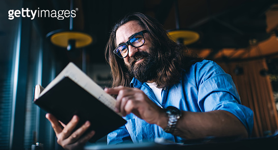 Smiling mature man in with long brunette hair spending free time on interesting literature hobby, positive caucasian male 40 years turn pages in book satisfied with leisure and self education in cafe