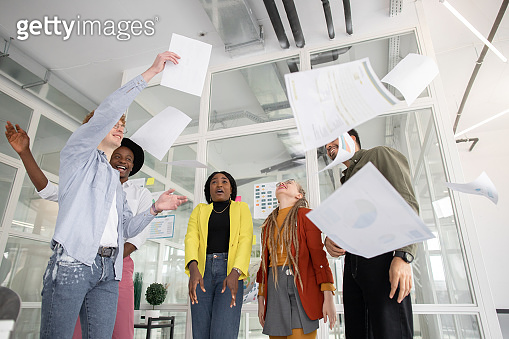 Startup team throwing up documents after meeting