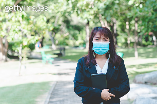 business woman wearing face mask hold smartphone tablet standing in park with sunrise and blur nature background. business new normal with corona virus or covid-19.
