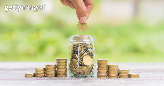 money saving, business financial growth, economy budget and investment concept. hand of business man put golden coin on coins stack growth up on green blur nature background.