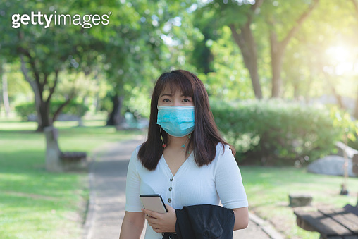attractive business woman wearing face mask hold smartphone standing in park with sunrise and blur nature background. business new normal with corona virus or covid-19.
