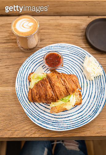 Croissant with grilled cheese and salad on plate and cup of cappuccino with latte art, wooden table in cafe or coffee shop. Tasty sandwich. Breakfast or lunch. Top view.