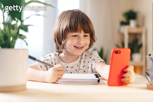 Back to school. Boy at home with phone