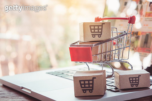 Online shopping. cardboard box with a shopping cart logo in a trolley on laptop keyboard. Shopping service on The online web. offers home delivery