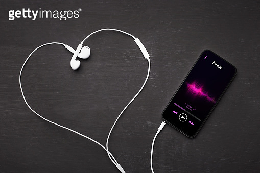 Mobile phone with music player app open and earphones shaping love heart symbol.