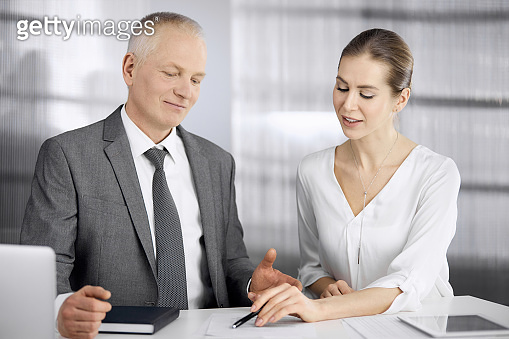 Elderly businessman and woman sitting and communicating in office. Adult business people or lawyers working together as a partners and colleagues at meeting. Teamwork and cooperation concept