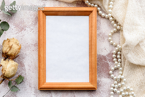 Romantic natural gentle background-clean photo frame and twigs of dry grass and flowers. Top view, close-up, and copy space. Wedding and gift fund