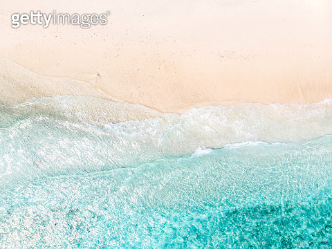 Aerial view of clear sea waves and white sandy beach in summer.