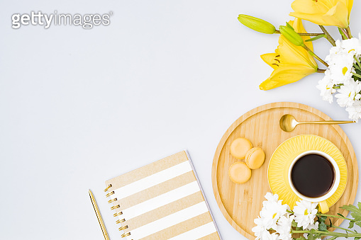 Flat lay workspace with notebook, cup of coffee and yellow lilies on a light background