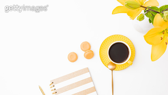 Flat lay workspace with notebook, macaroons, cup of coffee and yellow lilies on white background