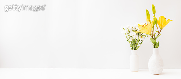 Home interior with decor elements. Yellow lilies in a vase on a light background