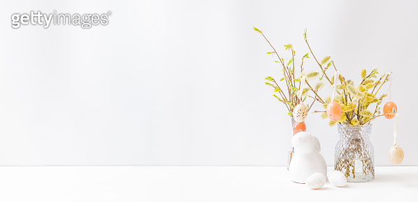 Home interior with easter decor. Willow branches in a vase, easter eggs on a light background
