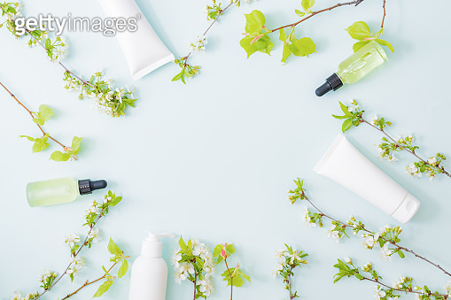 Flat lay composition with cosmetics and spring flowers on a light background