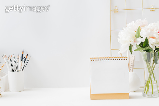 Home office desktop with mood board, books, office supplies on a light background