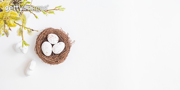 Flat lay easter composition with willow branches in a vase and easter eggs on a light background