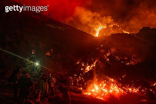 People observing volcano eruption in Iceland