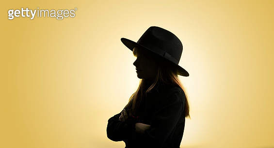Silhouette of young girl with a hat
