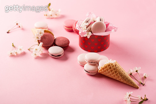 Rose macaroons in gift box, Cherry blossoms, empty envelope. Sweet macarons present on pink background.