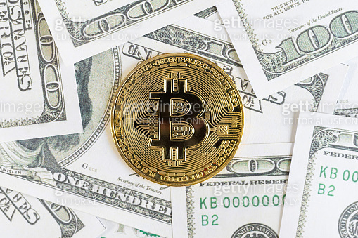 Bitcoin cryptocurrency golden coins and dollar bill in background