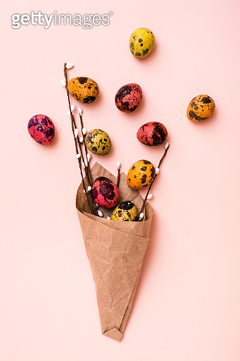 Happy Easter. Bouquet of painted quail eggs and pussy willow branches wrapped in brown paper on pink background. Vertical view
