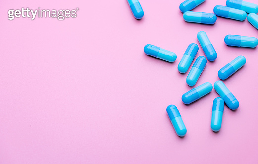 Blue capsule pills on pink background. Blue capsule pills with copy space. Pharmaceutical industry. Community pharmacy product. Drug use in pregnancy woman and lactation and elderly people topics.