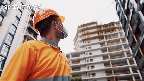 Construction worker wearing safety equipment. KN 95 mask. Corona mask. Covid-19 protective respirator. Coronavirus outbreak. Builder works in protective equipment respirator and hard hat