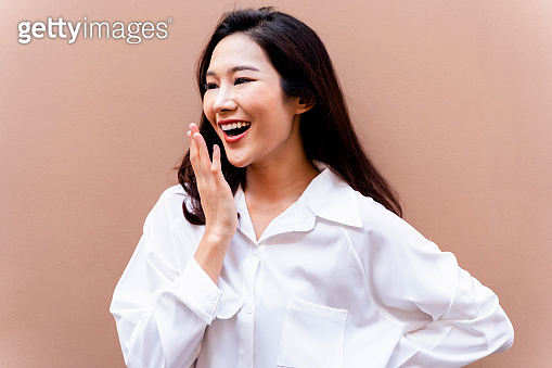 20s young Asian happy millenial woman in white shirt in clean background smiling and laughing confidently with beautiful teeth. Portrait of beauty skin care and oral care concept.