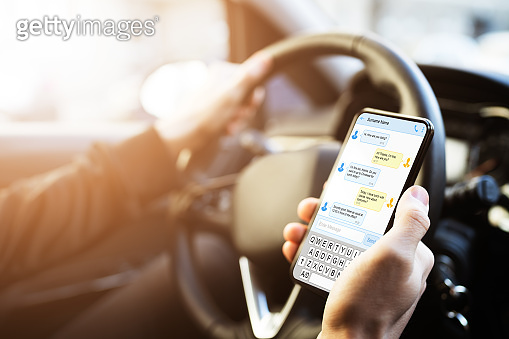 Man Typing Text Message On Phone While Driving Car