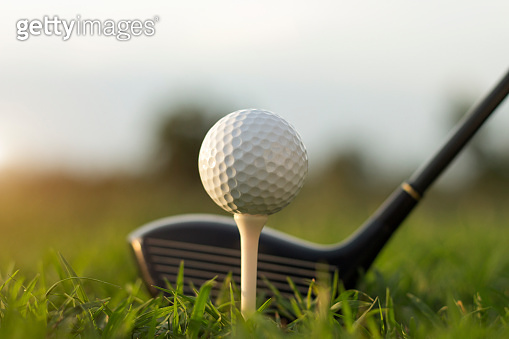 Golf clubs and golf balls on a green lawn in a beautiful golf course with morning sunshine