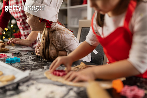 Cut out shot of two little girls and their mother making gingerbread cookies