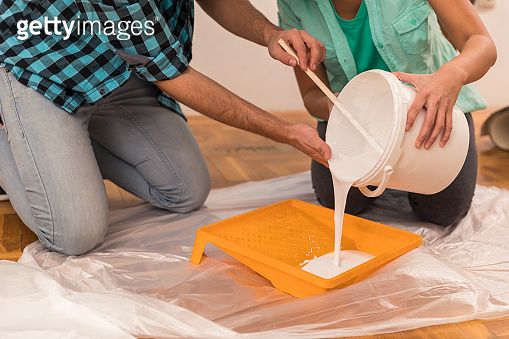 Young couple pouring white paint in a tray on the floor