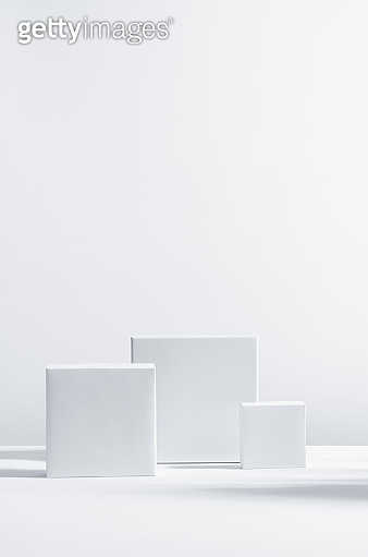 Elegant modern geometric style of showcase for cosmetics product display - white square podiums in sunlight with shadow in white background, vertical.