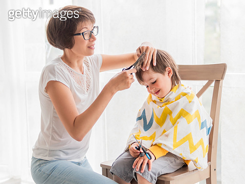 Mother cuts her son's hair by herself. Little boy sits, covered with cloth, and holds pair of scissors. New normal in case of coronavirus COVID-19 quarantine and lockdown. Beauty at home lifestyle.