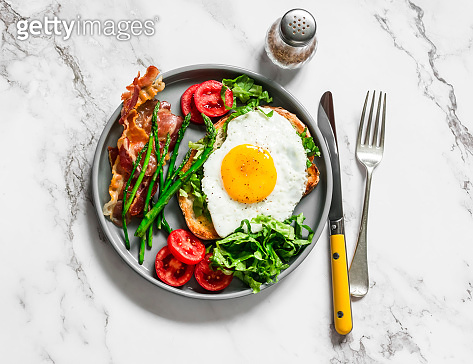 Delicious brunch - fried egg on toast, bacon, asparagus, tomatoes on a light marble background, top view