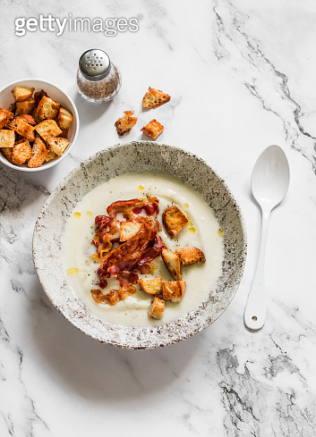 Cauliflower puree soup with bacon and crackers on a marble background, top view. Delicious comfort food concept