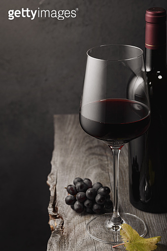 A glass of red wine, grapes and a bottle on an old wooden table. Dark bac