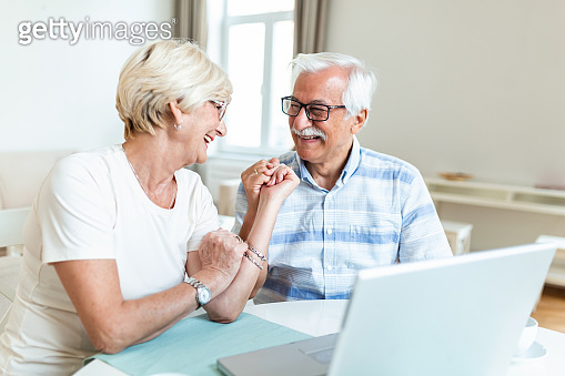 Senior couple is talking online via video connection on the laptop. Having nice time withfriends and family via video call.Holding their hands together