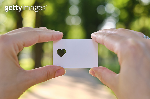 White card with a cut out heart in the hands of a girl in the rays of the sun. Close-up postcard. Form for congratulations. Romantic invitation. Mockup. Empty space for a message or invitation