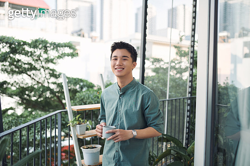 happy man contemplating views with coffee cup on a balcony