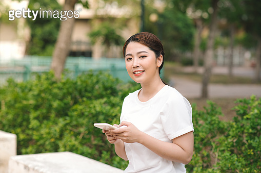 Photo of a happy smiling young woman in nature green park outdoors using mobile phone.