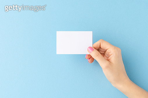 Female hand showing empty business card on blue background. Flat lay