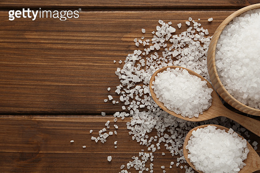 Natural sea salt on wooden table, flat lay. Space for textu