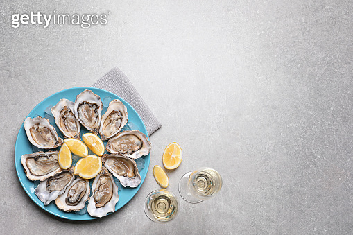 Fresh oysters with lemon and glasses of champagne on grey table, flat lay. Space for text