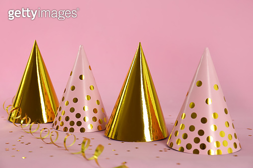Colorful party hats and confetti on pink background