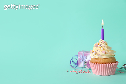 Birthday cupcake with burning candle, gift box  and sprinkles on turquoise background. space for text