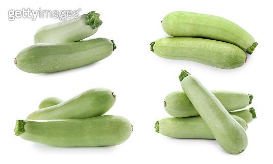 Set of fresh ripe zucchinis on white background