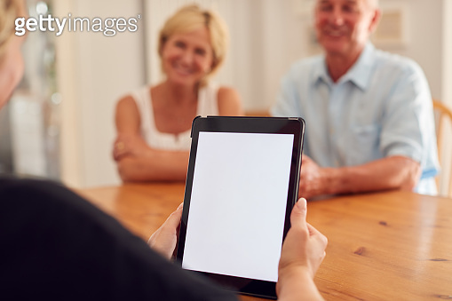 Close Up On Blank Screen Of Digital Tablet As Retired Couple Meeting With Financial Advisor At Home