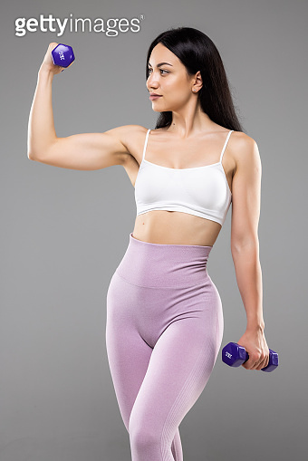 Young attractive happy latin woman in sport clothes with beautiful smile holding weight dumbbell doing fitness workout isolated on white background